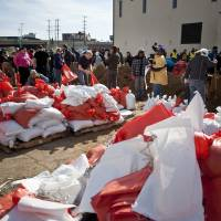 Photo - Volunteers fill sand bags Sunday, April 21, 2013 at the city's public works facility on Market street in Grand Rapids, Mich. (AP Photo/The Grand Rapids Press, Sally Finneran)