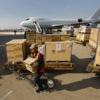 Photo -   A Syrian airport worker carries a box with equipment for the UN observers at the Damascus airport in Syria, Tuesday, May, 8, 2012. Special envoy Kofi Annan is to brief the U.N. Security Council on Tuesday about the situation in the country, where about 40 U.N. observers are trying to calm the situation. U.N. officials hope to deploy a larger force of up to 300 observers. (AP Photo/Muzaffar Salman)