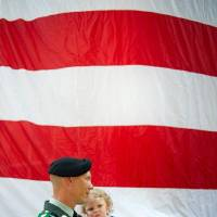 "Photo -  Jacob Long, of the Georgia Army National Guard, holds his 14-month-old daughter, Charlotte, while listening to the song ""God Bless America"" during a Memorial Day ceremony, Monday, May 30, 2011, in Roswell, Ga. (AP Photo/Rich Addicks) ORG XMIT: GARA111"