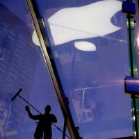 Photo -   FILE - In this July 21, 2011 file photo, a window washer works atop the cube-like structure of glass that houses the Apple Store showroom in the Upper West Side of Manhattan. Apple Inc. said it will announce the outcome of its internal discussion concerning its enormous cash balance on Monday morning, March 19, 2012. (AP Photo/Craig Ruttle, File)