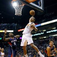 Photo - Phoenix Suns' Gerald Green (14) dunks over Atlanta Hawks' Shelvin Mack (8) and Kyle Korver during the second half of an NBA basketball game, Sunday, March 2, 2014, in Phoenix. The Suns won 129-120. (AP Photo/Matt York)