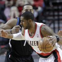 Photo - Portland Trail Blazers forward LaMarcus Aldridge, right, works his way inside against Minnesota Timberwolves forward Derrick Williams during the first quarter of an NBA basketball game in Portland, Ore., Saturday, March 2, 2013. (AP Photo/Don Ryan)