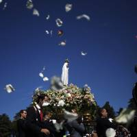 Photo - AP10ThingsToSee - Worshippers throw flower petals to the statue of the Our Lady of Fatima, in Fatima, Portugal, Tuesday, May 13, 2014. Every year on May 12 and 13 thousands of Catholic pilgrims arrive to Fatima Sanctuary to attend Masses and pray in honor of the Virgin Mary, where it is believed she was witnessed by three shepherd children in 1917. (AP Photo/Francisco Seco)