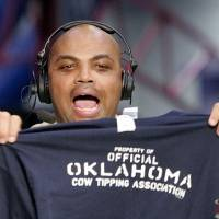"""Photo -  Charles Barkley holds up an """"Oklahoma Cow Tipping Association"""" shirt presented to him by KWTV anchor Kelly Ogle and news director Blaise Labbe (cq BLAISE LABBE) on the set of TNT's Inside the NBA at the NBA Jam Session, part of the NBA All-Star events in Houston, Texas, Febraury 16, 2006. Barkley has agreed to take up the challenge of Ogle and Labbe to visit Oklahoma. By Nate Billings, The Oklahoman."""