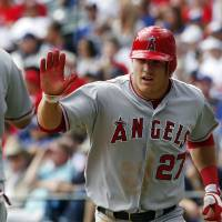 Photo -   Los Angeles Angels' Mike Trout (27) high-fives Kendrys Morales (8) after scoring on a single by Albert Pujols during the third inning of the first baseball game of a doubleheader, Sunday, Sept. 30, 2012, in Arlington, Texas. The Angels won 5-4. (AP Photo/LM Otero)