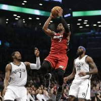 Photo - Miami Heat guard Dwyane Wade (3) goes up for a layup, between Brooklyn Nets guard Joe Johnson (7) and forward Reggie Evans (30) during the first half of on NBA basketball game Wednesday, Jan. 30, 2013, in New York. (AP Photo/Kathy Willens)