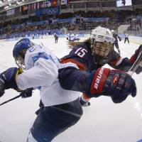 Photo - Nina Tikkinen of Finland and Anne Schleper of the United States battlers from control of the puck against the glass during the second period of the women's ice hockey game at the Shayba Arena during the 2014 Winter Olympics, Saturday, Feb. 8, 2014, in Sochi, Russia. (AP Photo/Matt Slocum)