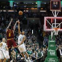 Photo - Cleveland Cavaliers' Earl Clark (6) fails to make a 3-pointer over Boston Celtics' Avery Bradley (0) with no time left on the clock in the fourth quarter of an NBA basketball game in Boston, Saturday, Dec. 28, 2013. The Celtics won 103-100. (AP Photo/Michael Dwyer)