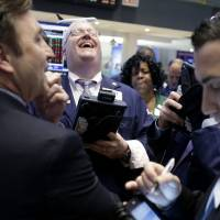 Photo - A trader laughs Thursday while working on the floor of the New York Stock Exchange.  AP Photo