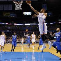 Photo - Oklahoma City's Russell Westbrook, center, shoots a layup in front of Orlando's Jameer Nelson during Sunday's game. Photo by Sarah Phipps, The Oklahoman