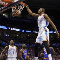 Photo - Oklahoma City's Kevin Durant (35) dunks the ball in front of Serge Ibaka (9), New York's Raymond Felton (2) and Iman Shumpert (21) during an NBA basketball game between the New York Knicks and the Oklahoma City Thunder at Chesapeake Energy Arena in Oklahoma City, Sunday, Feb. 9, 2014. Photo by Nate Billings, The Oklahoman