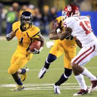 Photo -   West Virginia's Tavon Austin (1) carries the ball as J.D. Woods (81) blocks Oklahoma's Aaron Colvin (15) during the fourth quarter of their NCAA college football game against Oklahoma in Morgantown, W.Va., on Saturday, Nov. 17, 2012. Oklahoma won 50-49. (AP Photo/Christopher Jackson)