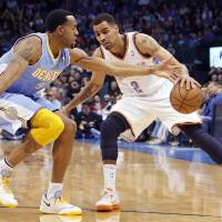 Photo - Oklahoma City's Thabo Sefolosha (2) drives past Denver's Andre Iguodala (9) during the NBA basketball game between the Oklahoma City Thunder and the Denver Nuggets at the Chesapeake Energy Arena on Wednesday, Jan. 16, 2013, in Oklahoma City, Okla.  Photo by Chris Landsberger, The Oklahoman