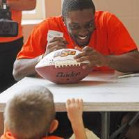 Photo - Oklahoma State safety Larry Stephens signs a football for five-year-old Aiden Bruner of Winfield, Kansas, at Oklahoma State's fan appreciation day in Gallagher Iba Arena in Stillwater on Saturday, August 2, 2014. Photo by KT King, The Oklahoman
