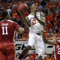Photo - Oklahoma State's Le'Bryan Nash (2) shoots a lay up in between Oklahoma's Isaiah Cousins (11) and Oklahoma's Amath M'Baye (22) during the Bedlam men's college basketball game between the Oklahoma State University Cowboys and the University of Oklahoma Sooners at Gallagher-Iba Arena in Stillwater, Okla., Saturday, Feb. 16, 2013. Photo by Sarah Phipps, The Oklahoman