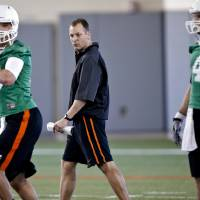 Photo - Oklahoma State football offensive coordinator Mike Yurcich watches quarterbacks Mason Rudolph (10) and J.W. Walsh (4) go through drills during the first day of spring football practice at Oklahoma State University in Stillwater, Okla., on Monday, March 10, 2014.  Photo by Chris Landsberger, The Oklahoman