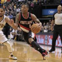 Photo - Portland Trail Blazers point guard Damian Lillard, front right, drives past Indiana Pacers point guard D.J. Augustin in the first half of an NBA basketball game in Indianapolis, Wednesday, Dec. 5, 2012. (AP Photo/Michael Conroy) ORG XMIT: NAF106