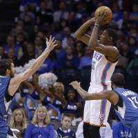 Photo - Oklahoma City Thunder forward Kevin Durant (35) shoots over Minnesota Timberwolves forward Kevin Love (42) and guard Alexey Shved (13) in the first quarter of an NBA basketball game in Oklahoma City, Sunday, Dec. 1, 2013. (AP Photo/Sue Ogrocki)