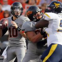 Photo - Oklahoma State's Clint Chelf (10) looks to pass in the first quarter during a college football game between Oklahoma State University (OSU) and West Virginia University (WVU) at Boone Pickens Stadium in Stillwater, Okla., Saturday, Nov. 10, 2012. Photo by Nate Billings, The Oklahoman