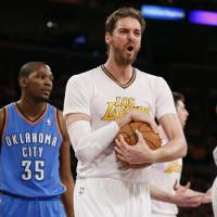 Photo - Los Angeles Lakers center Pau Gasol, center, reacts after a foul was called against teammate Ryan Kelley, rear right, as Oklahoma City Thunder small forward Kevin Durant, left, looks on during the first half of an NBA basketball game in Los Angeles, Sunday, March 9, 2014. (AP Photo/Danny Moloshok)