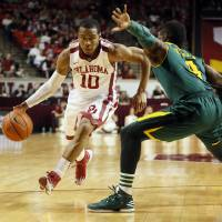 Photo - Oklahoma's Jordan Woodard (10) drives against Baylor's Gary Franklin (4) during an NCAA men's college basketball game between Baylor and the University of Oklahoma (OU) at Lloyd Noble Center in Norman, Okla., Saturday, Feb. 8, 2014. Photo by Nate Billings, The Oklahoman