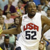 Photo - Oklahoma City Thunder's Kevin Durant (52) drives by Denver Nuggets' Kenneth Faried (33) during the USA Basketball Showcase game Friday, Aug. 1, 2014, in Las Vegas. (AP Photo/John Locher)