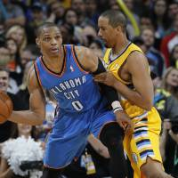 Photo - Oklahoma City Thunder guard Russell Westbrook, left, looks to pass under pressure from Denver Nuggets guard Andre Miller in the third quarter of an NBA basketball game in Denver on Sunday, Jan. 20, 2013. The Nuggets won 121-118 in overtime. (AP Photo/David Zalubowski) ORG XMIT: CODZ118