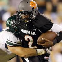 Photo - Norman High quarterback Jakcob Dean is brought down by Norman North's Mason Volk at Gaylord Family-Oklahoma Memorial Stadium in Norman, Okla., on Thursday, Sept. 5, 2013. Photo by Steve Sisney, The Oklahoman