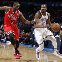 Photo - Oklahoma City's Kevin Durant (35) tries to get past Chicago's Luol Deng (9) during the NBA game between the Oklahoma City Thunder and the Chicago Bulls at Chesapeake Energy Arena in Oklahoma City, Saturday, Feb. 23, 2013. Photo by Sarah Phipps, The Oklahoman