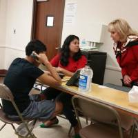 Photo - This provided photo was posted to Mary Fallin's Twitter account Friday, June 20, 2014, depicting Fallin sitting in with a caseworker at Fort Sill who was helping an immigrant minor try to reach relatives in the U.S.