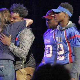 John Marshall Mid-High principal Aspasia Carlson hugs Keyshawn Shells before he talked about his good friend C.J. Davis during a memorial service at People's Church on Monday night. (Photo by Steve Gooch)