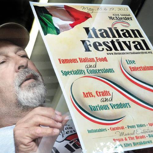 Bob Lenardo puts up a sign for the Italian Festival, which will be Saturday and Sunday at the Southeast Expo Center. (McAlester News-Capital photo)
