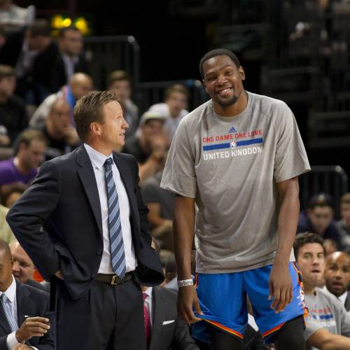 Oklahoma City Thunder's Kevin Durant, right, stands with Head Coach Scott Brooks during the team's NBA preseason basketball game against Philadelphia 76ers at the Phones 4u Arena in Manchester, England, Tuesday, Oct. 8, 2013. (AP Photo/Jon Super) ORG XMIT: MJS109