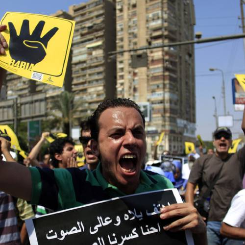 """Supporters of Egypt's ousted President Mohammed Morsi chant slogans and hold placards showing an open palm with four raised fingers, which has become a symbol of the Rabaah al-Adawiya mosque, where Morsi supporters had held a sit-in for weeks that was violently dispersed on Aug. during a protest in Cairo, Egypt, Friday, Sept. 6, 2013. Thousands of protesters flowed out of mosques on Friday in Muslim Brotherhood-led rallies against the military-backed government a day after a car bomb in the Egyptian capital marked a substantial escalation in EgyptÂ's violent turmoil. Arabic writing on the black poster reads """" Chant loud we Brooke the voice with death.""""(AP Photo/Khalil Hamra)"""