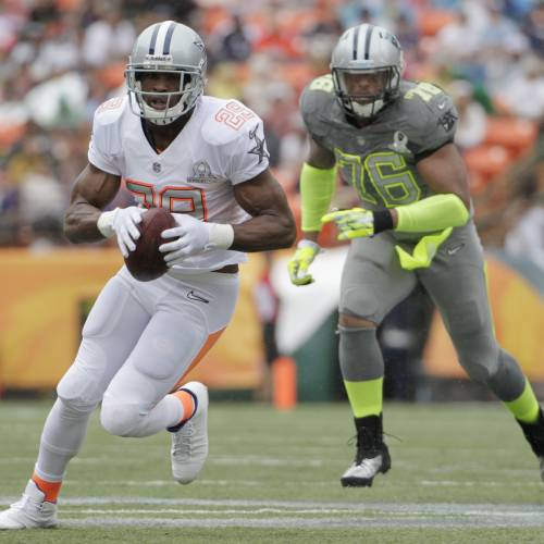 Dallas Cowboys running back DeMarco Murray (29) of Team Rice runs with the football after catching a pass in the first quarter quarter of the NFL Pro Bowl football game Sunday, Jan. 26, 2014, in Honolulu. Carolina Panthers defensive end Greg Hardy (76) of Team Sanders looks on during the play. (AP Photo/Eugene Tanner)