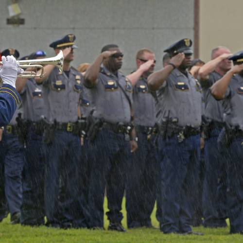 Members of the Baton Rouge Police Department salute as a member of the Louisiana State Police...