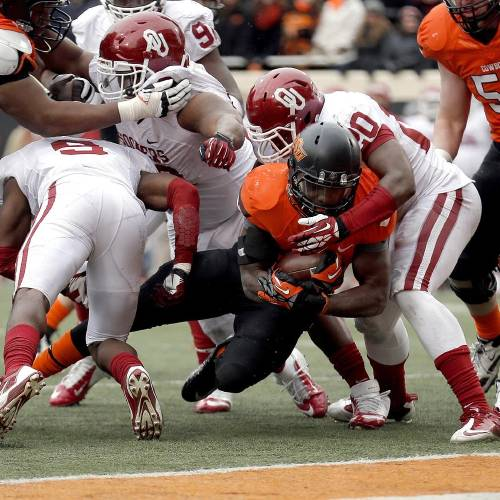 Oklahoma State's Desmond Roland (26) is stopped short of the goal line by Oklahoma's Frank Shannon (20) during the Bedlam college football game between the Oklahoma State University Cowboys (OSU) and the University of Oklahoma Sooners (OU) at Boone Pickens Stadium in Stillwater, Okla., Saturday, Dec. 7, 2013. OU won 33-24. Photo by Sarah Phipps, The Oklahoman