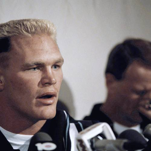 With head coach Barry Switzer of the Oklahoma Sooners, right, reacting unhappily in the background, All-American linebacker Brian Bosworth speaks to the press about his being barred from playing in the 53rd Annual Orange Bowl Classic New Years Day, Friday, Dec. 26, 1986, Miami Beach, Fla. Bosworth was barred because steroids were found in his system but he said he deserves a right to give my body the ultimate challenge and be as healthy as I can be. (AP Photo/Judy Sloan)