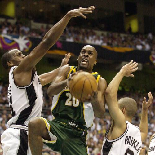 NBA BASKETBALL PLAYOFFS: Seattle SuperSonics guard Gary Payton (20) goes to the basket as San Antonio Spurs' Malik Rose, left, and Tony Parker defend during the third quarter of their first-round playoff game in San Antonio, Monday, April 22, 2002. (AP Photo/Eric Gay)