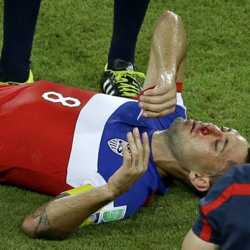 United States' Clint Dempsey lies on the pitch after being kicked in his face during the group G World Cup soccer match between Ghana and the United States at the Arena das Dunas in Natal, Brazil, Monday, June 16, 2014. (AP Photo/Hassan Ammar)