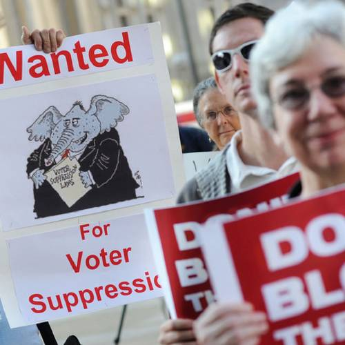 Demonstrators hold signs during a voter ID rally September 13, 2012 in Philadelphia, Pennsylvania. The Pennsylvania Supreme Court held a hearing on Pennsylvania's state Supreme Court justices on whether a law requiring photo identification from each voter should take effect for the Nov. 6 presidential election. (William Thomas Cain/MCT via Getty Images)