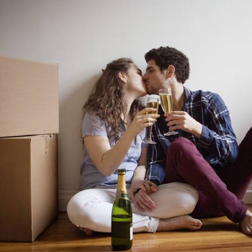 Couple Kissing And Toasting To Their New Home