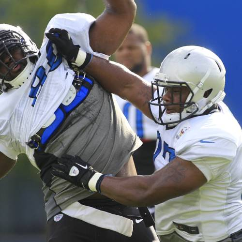 Detroit Lions defensive end Ronnell Lewis, right, stiff arms Detroit Lions defensive tackle Andre Fluellen during NFL football training camp in Allen Park, Mich., Tuesday, July 31, 2012. (AP Photo/Carlos Osorio) ORG XMIT: MICO108