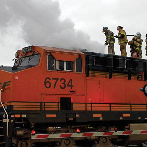 Firefighters extinguish a blower motor fire in the engine compartment of a BNSF train. (Claremore Progress photo)