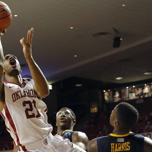 Oklahoma's Cameron Clark (21) drives to the basket past West Virginia's Remi Dibo (0) and Eron Harris (10) during the college basketball game between the University of Oklahoma Sooners (OU) and West Virginia University Mountaineers (WVU) at the Lloyd Nobel Center in Norman, Okla. on Wednesday, March 5, 2014. Photo by Chris Landsberger, The Oklahoman