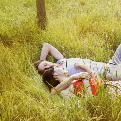 Couple laying in grass relaxing.