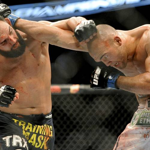 Johny Hendricks, left, and Robbie Lawler exchange punches during a UFC 171 mixed martial arts welterweight title bout, Saturday, March 15, 2014, in Dallas. Hendricks won by decision. (AP Photo/Matt Strasen)