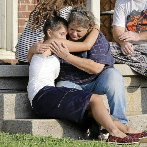 Lisa Kepler (left), 18, hugs Pam Wilkins on the steps of Wilkins' home the morning after Jeremey Lake, Wilkins' nephew, was fatally shot. Kepler was dating Lake, and her parents, both Tulsa police officers, have been arrested in connection with the fatal shooting. MICHAEL WYKE/Tulsa World