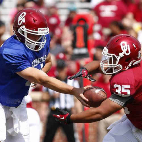 Oklahoma quarterback Justice Hansen (4) hands off a pass to running back Leo Luna (35) during the second half of the annual Oklahoma Spring Football game in Norman, Okla. on Saturday, April 12, 2014. (AP Photo/Alonzo Adams)