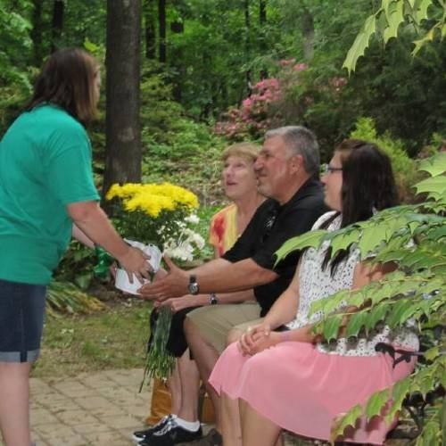 "Debbie Deakins, Grove Girl Scout Troop 1831 troop leader, gives a potted plant of daisies, as a remembrance of the Girl Scout Daisy Troop, to Mike and Julie Lewandowski, the parents of Jessica 'Jessie"" Lewandowski. (Grove Sun photo)"